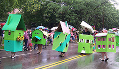 People dressed as houses parading down street